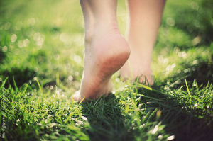 Walking barefoot across the grass.