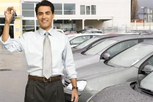Man holding car keys at car dealership