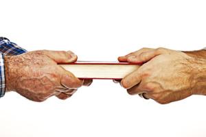Closeup of mature mans hand giving a book to his son,conceptua