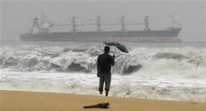 A man holding an umbrella watches large waves on the Marina beach as a cargo ship passes after Cyclone Thane hit the southern Indian state of Tamil Nadu