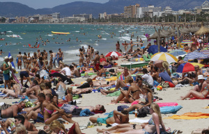 Tourists crowd Palma de Mallorca's Arenal beach on the Spanish Balearic island of Mallorca