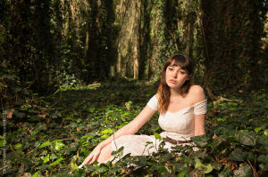 Young, beautiful woman sitting in the middle of the forest wearing a white dress